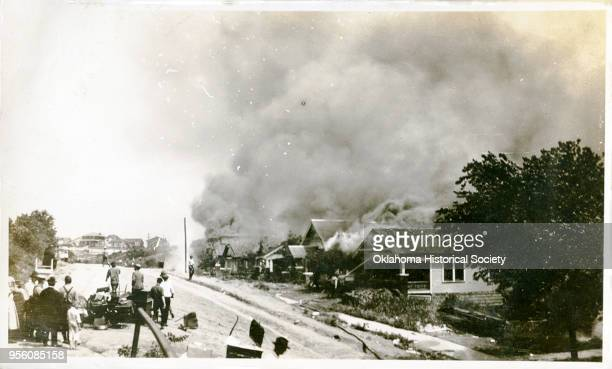 Group of people looking at smoke in the distance coming from damaged properties following the Tulsa Race Massacre, Tulsa, Oklahoma, June 1921.