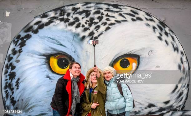Group of people make a selfie picture with an owl graffiti drawing on the background in central Moscow on January 12, 2019.