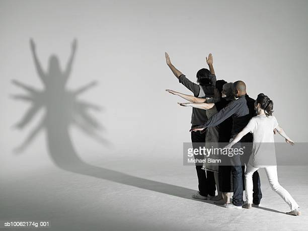 Group of people making star shaped shadow in front of light