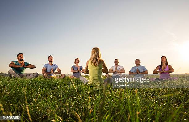 Group of people meditating during yoga class at sunset.