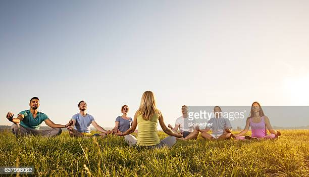Group of people meditating in lotus position at sunset.