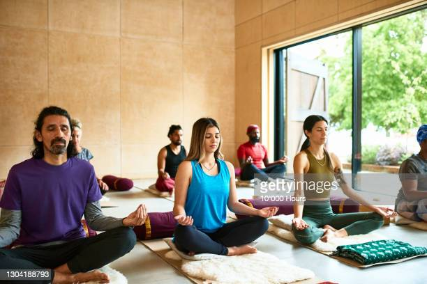group of people meditating in yoga class - buddhism stock pictures, royalty-free photos & images