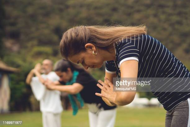 group of people meditating outdoors - kung fu yoga stock pictures, royalty-free photos & images