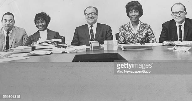 A group of people men and women forming a credit union seated at a table the board of directors June 17 1967