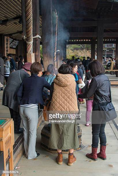 group of people offering incense - kiyomizu dera temple stock photos and pictures