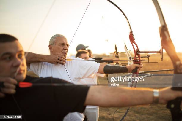 group of people on archery training - archery stock pictures, royalty-free photos & images
