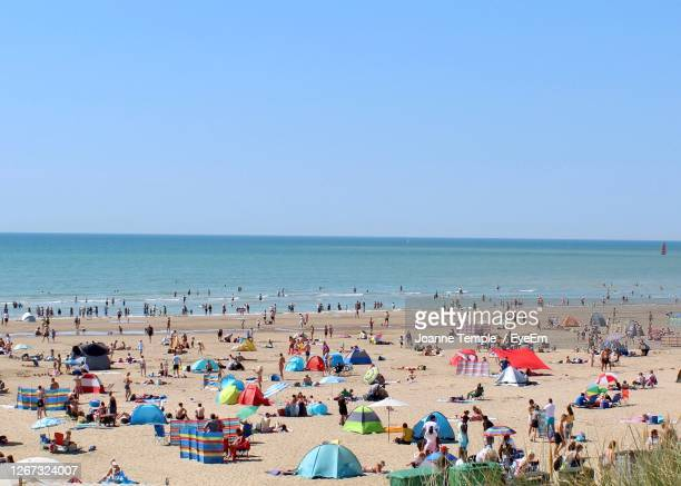 group of people on beach against clear sky - crowd stock pictures, royalty-free photos & images