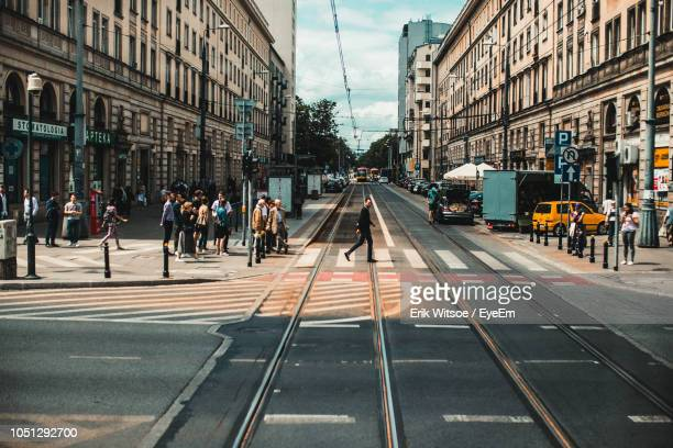 group of people on city street amidst buildings - warsaw stock pictures, royalty-free photos & images