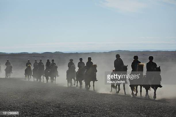 Group of people on horses riding in dust cloud