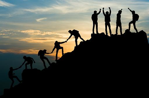 Group of people on peak mountain climbing helping team work , travel trekking success business concept 1009803562