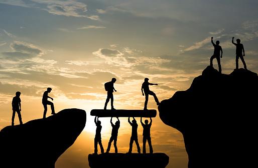 Group of people on peak mountain climbing helping team work , travel trekking success business concept 1135670850
