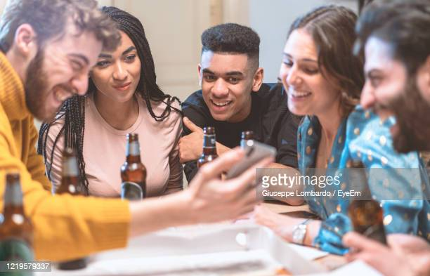 group of people on table having fun watching video movies on the smartphone screen - meme stock pictures, royalty-free photos & images