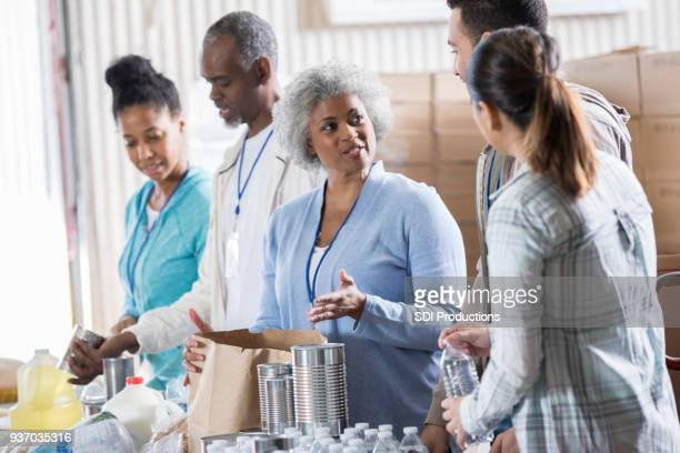 group of people organize donations during food drive - non profit organization stock pictures, royalty-free photos & images