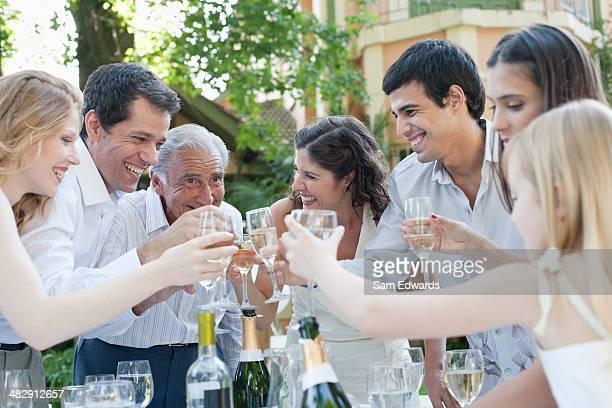 Gruppe von Personen im Freien lächelnd Anstoßen mit Champagner und