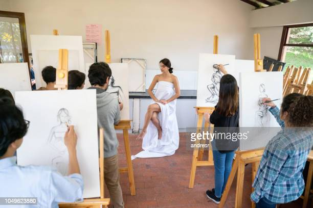 Group of people painting a live model in an art class