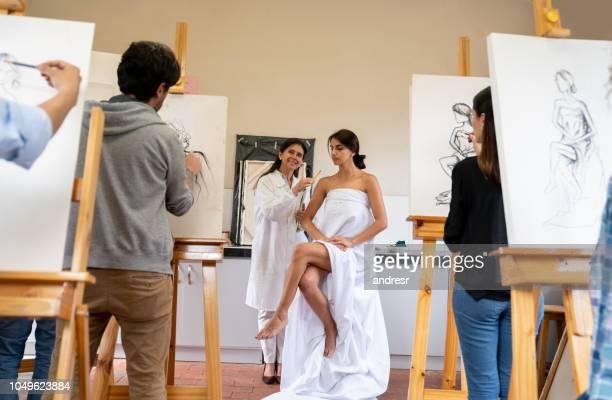 gruppe von menschen, die malerei eine live-modell in eine kunst-klasse - aktmodel stock-fotos und bilder