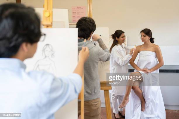 group of people painting a live model in an art class - modelo vivo imagens e fotografias de stock