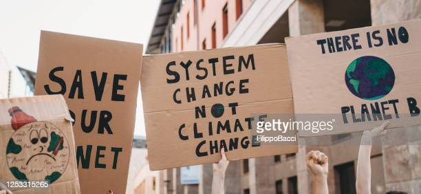 group of people participating in a protest against global warming - climate stock pictures, royalty-free photos & images