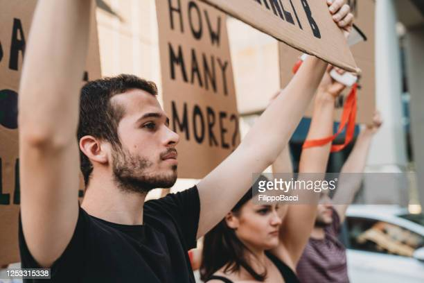 group of people participating in a social protest in the city - social justice concept stock pictures, royalty-free photos & images