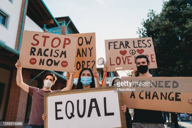 group of people participating in an anti-racism protest - anti racism stock pictures, royalty-free photos & images
