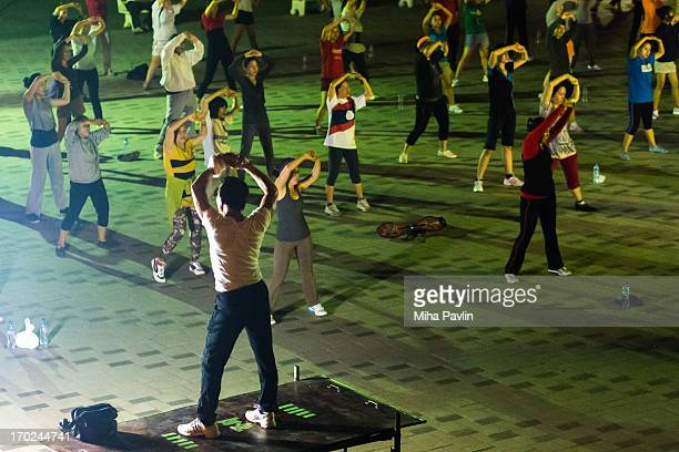 CONTENT] Group of people performing aerobic/recreation in park during nighttime