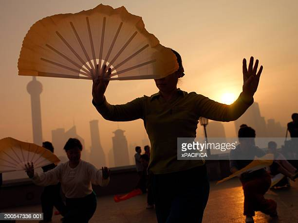 Group of people performing stretching exercises in front of Pudong skyline, Shanghai, China