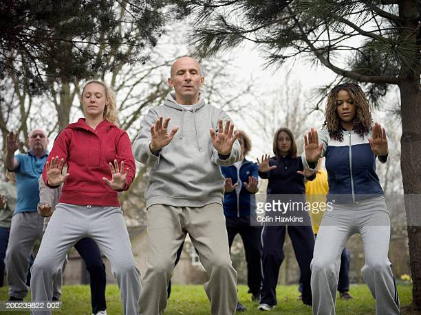 Group of people performing Tai Chi in park