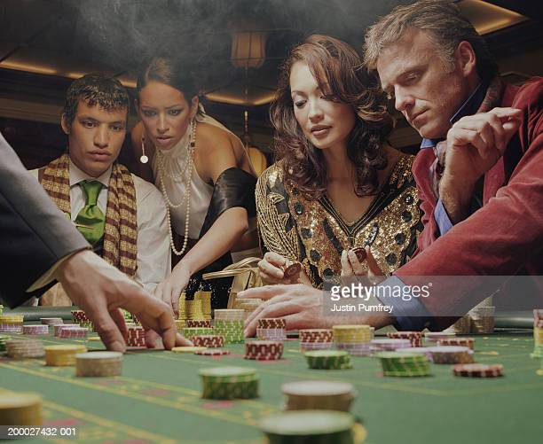 Group of people placing chips on casino table