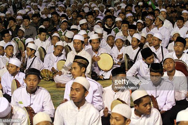 A group of people play frame drums and perform hymn as more than 50000 Indonesian Muslims gathered in Solo to protest against the attacks of the...