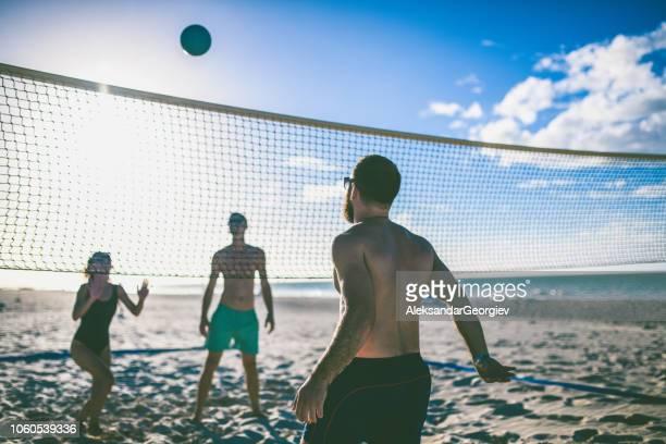 gruppe von menschen spielen beach-volleyball während eines urlaubs - strandvolleyball spielerin stock-fotos und bilder