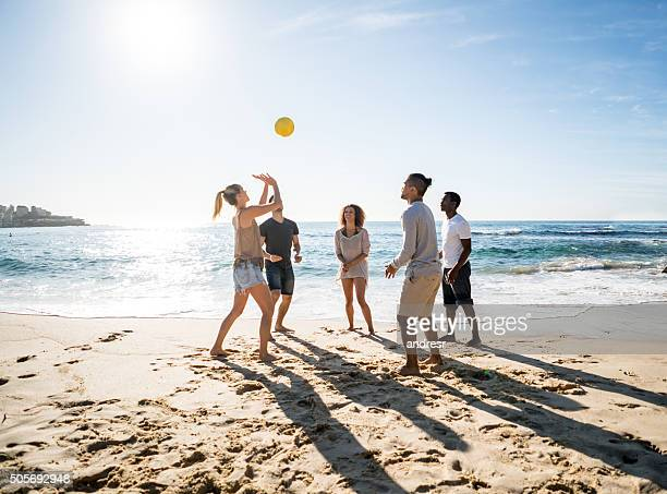 group of people playing beach volleyball - beachvolleybal stockfoto's en -beelden
