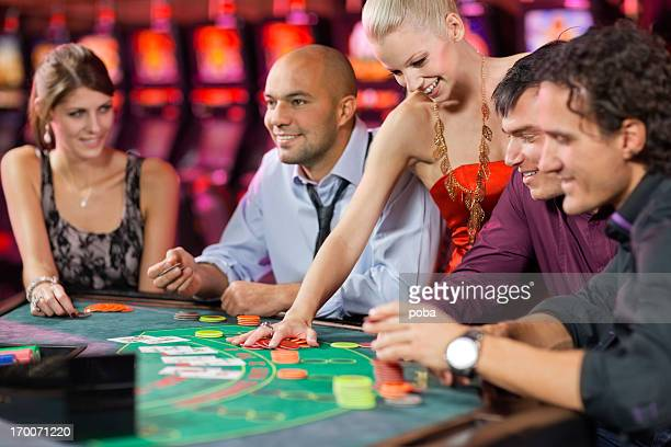 group of people playing blackjack in the casino
