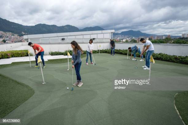 group of people playing mini golf - miniature golf stock photos and pictures