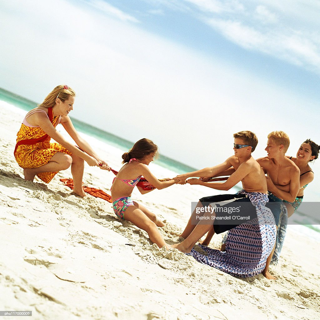 Group of people playing tug of war at the beach : Stockfoto