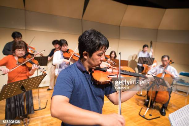 Group of people playing violin at concert hall