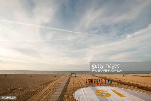 A group of people pose close to a banner reading 'SI' and an 'Estelada' placed on the sand of El Masnou beach near Barcelona on September 3 during an...