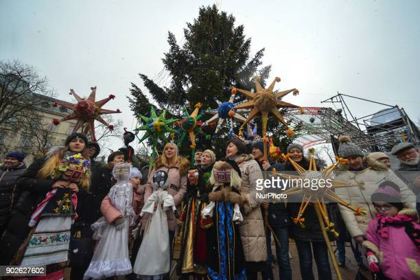 A group of people pose for a photo with their Christmas Stars in front of Christmas Tree near Lviv's Opera at the end of the Christmas Stars Parade...