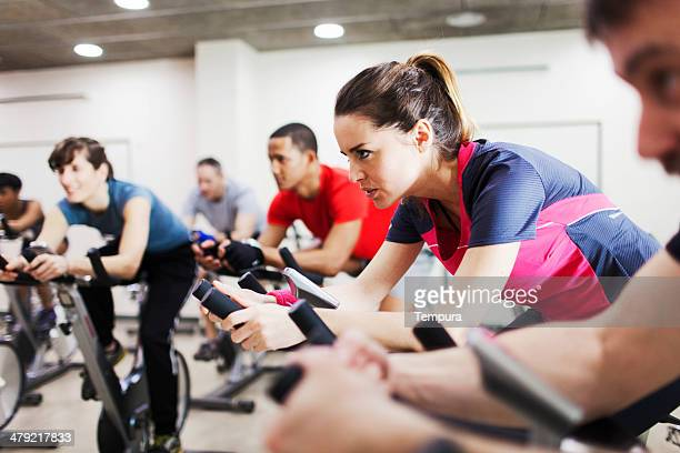group of people practicing sport in a gym. - peloton stock pictures, royalty-free photos & images