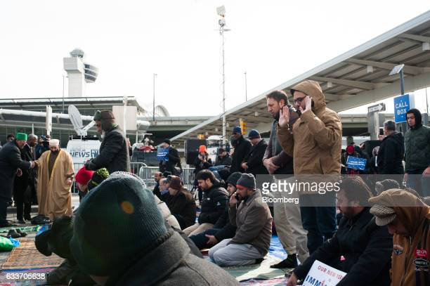 A group of people pray during an interfaith prayer and rally at John F Kennedy Airport to protest US President Donald Trump's travel ban on...