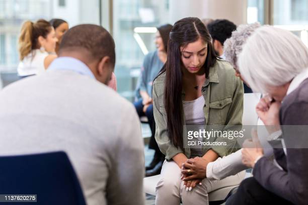 group of people pray for young woman - christianity stock pictures, royalty-free photos & images