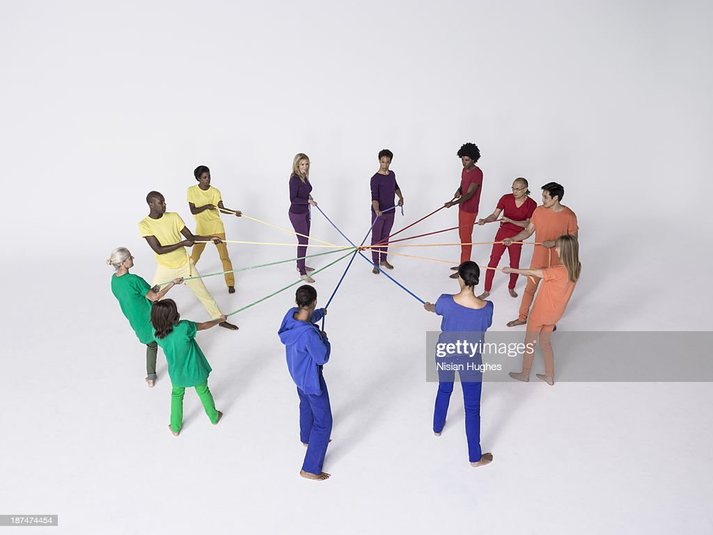 Group of people pulling connected color ropes : Stock Photo