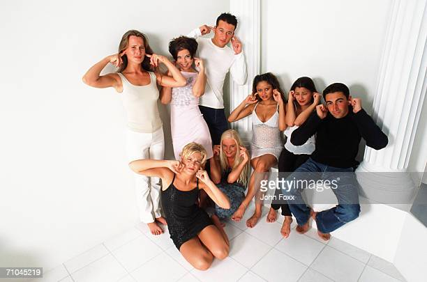 group of people putting fingers in ears  - fingers in ears stock pictures, royalty-free photos & images