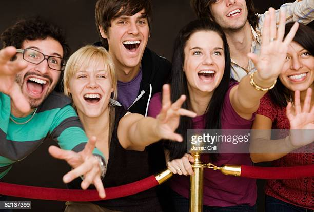 Group of people reaching across velvet rope