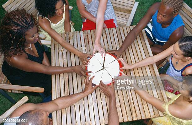 Group of people reaching for sliced cake on table, elevated view