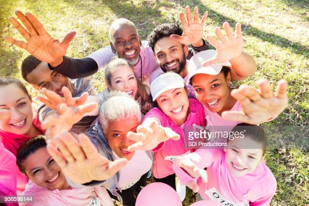 gruppe von menschen erreichen sie beim charity-event - überleben stock-fotos und bilder