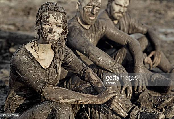 group of people relaxing after mud obstacle run