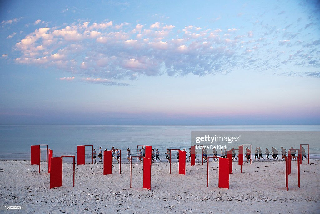 A group of people run past red doors to be used in an installation by surrealist artist, Andrew Baines at Henley Beach on December 13, 2012 in Adelaide, Australia. The installation was called 'Doorways To Potential'.
