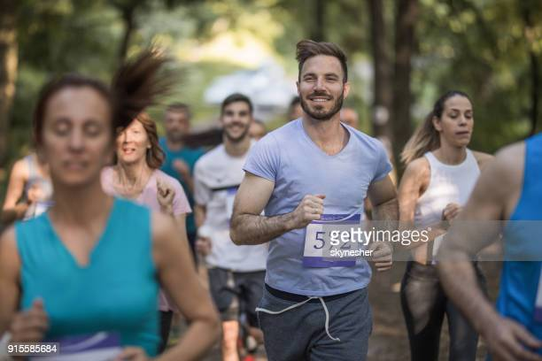 group of people running a marathon race in nature. - half_marathon stock pictures, royalty-free photos & images