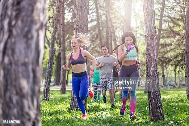 group of people running in park - spring racing stock photos and pictures