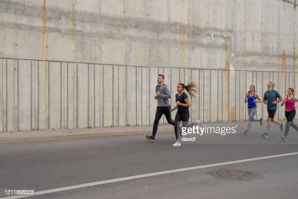 group of people running in the city - marathon stock pictures, royalty-free photos & images
